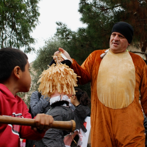 William Robles of Guadalupe holds a piñata of Donald Trump while a small boy hits it with a baseball bat on January 20th, 2017 at the Arizona State Capitol.