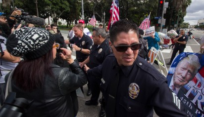 Sergeant Nieves of the Los Angeles Police Department forms a barrier between pro-imigrant marchers and Trump supporters outside city hall in downtown Los Angeles on February 18th, 2017.