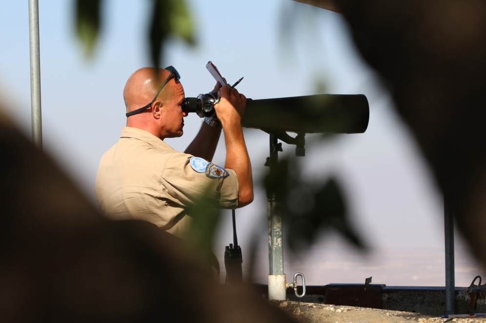 A UN officer look into Syria from atop a hill near the 1974 Syrian-Israeli ceasefire line in the Israeli-occupied Golan Heights on August 3rd, 2017. (Craig Johnson