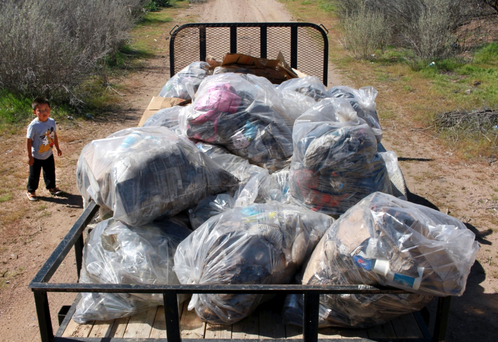 A child throws trash onto a trailer during a community cleanup on the San Carlos Apachie Indian Reservation in eastern Arizona on March 4th, 2017.