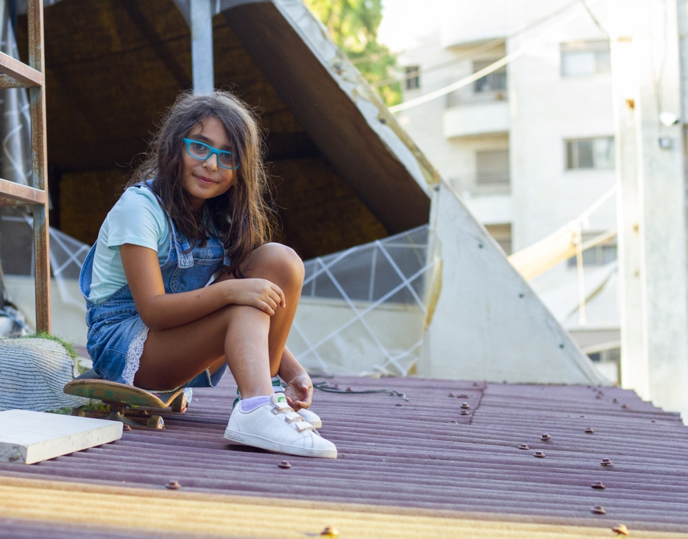 Alma, a young Palestinian skateboarder from Ramallah sits on a roof in the Israeli-occupied West Bank in July, 2019